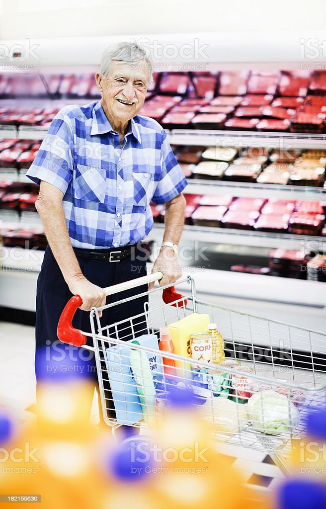 Cheerful old man pushes shopping cart past supermarket fridge stock photo