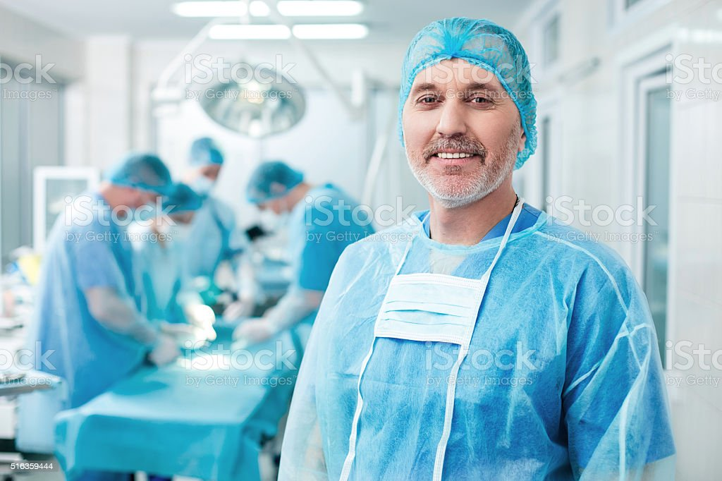 Cheerful old surgeon is examining the operation stock photo
