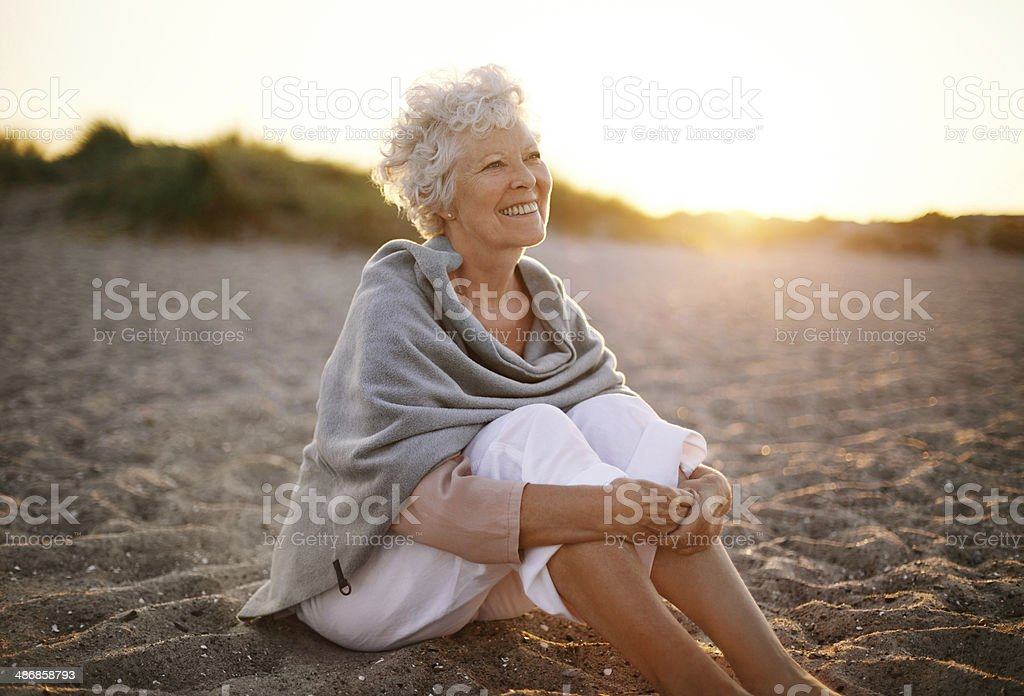 Cheerful old woman sitting on the beach stock photo