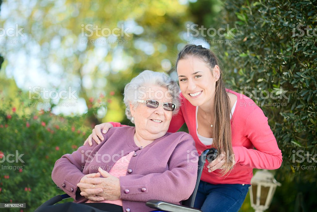 cheerful old woman wheelchair with young granddaughter outdoor in garden stock photo