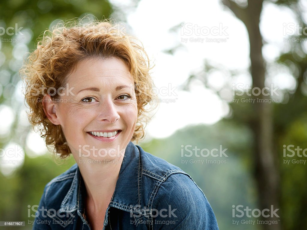 Cheerful older woman smiling outdoors stock photo