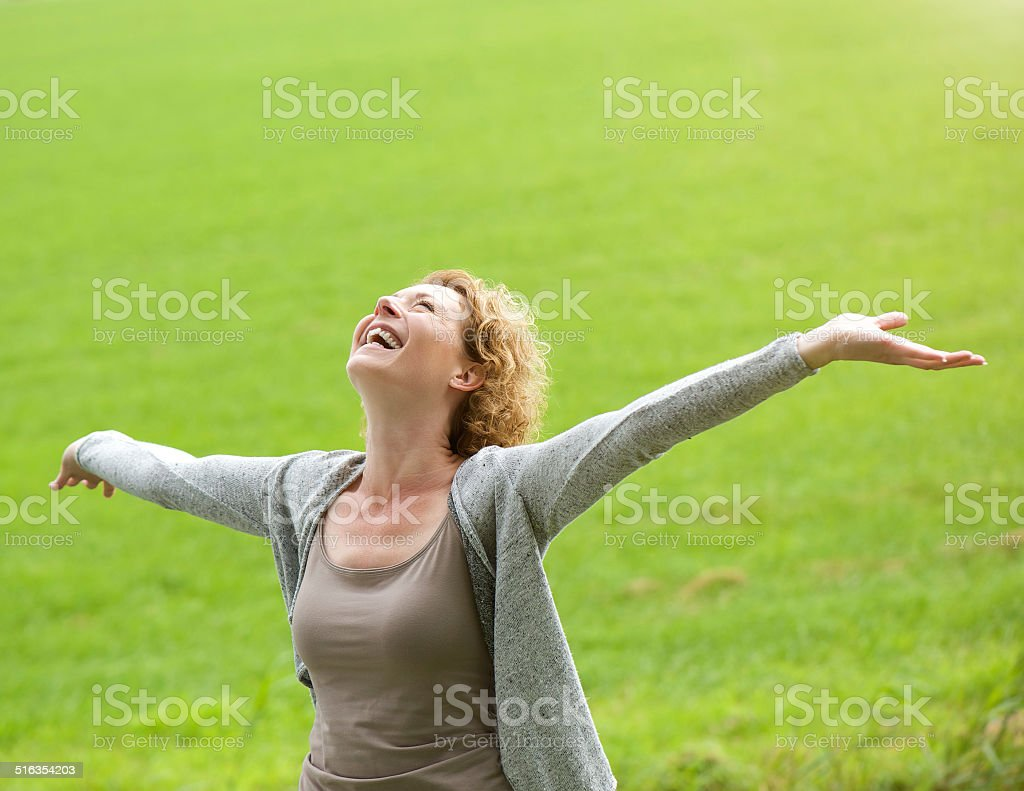 Cheerful older woman smiling with arms outstretched stock photo