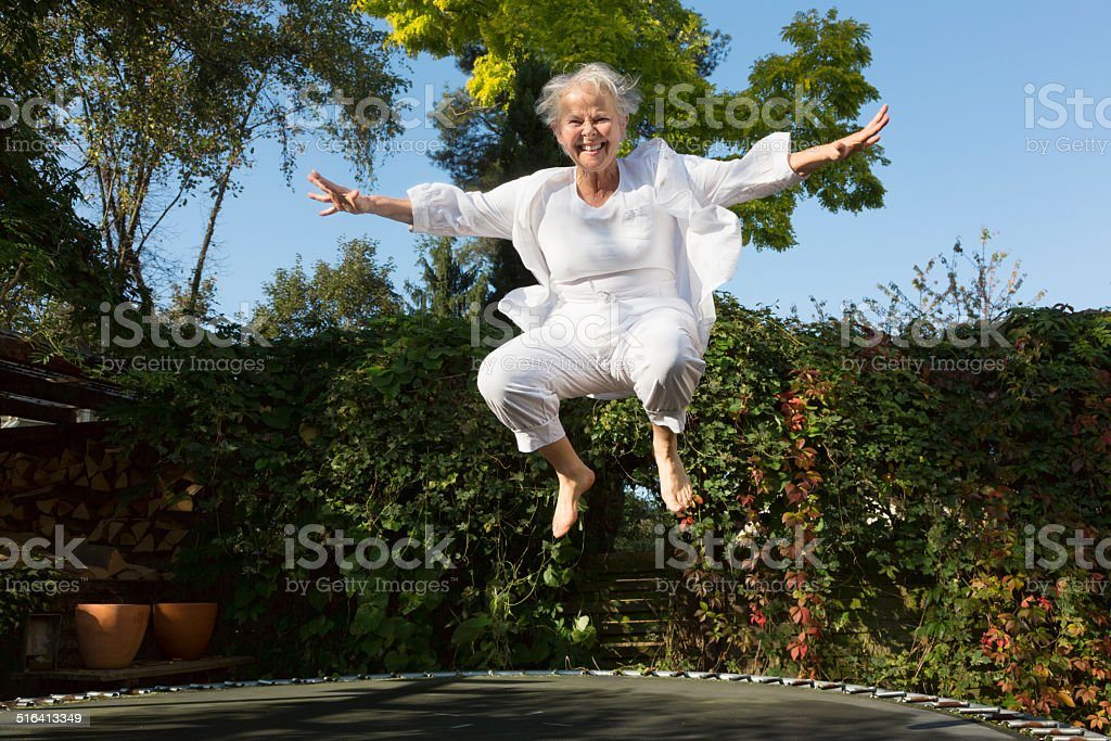 cheerful overweight senior woman jumping on trampoline stock photo