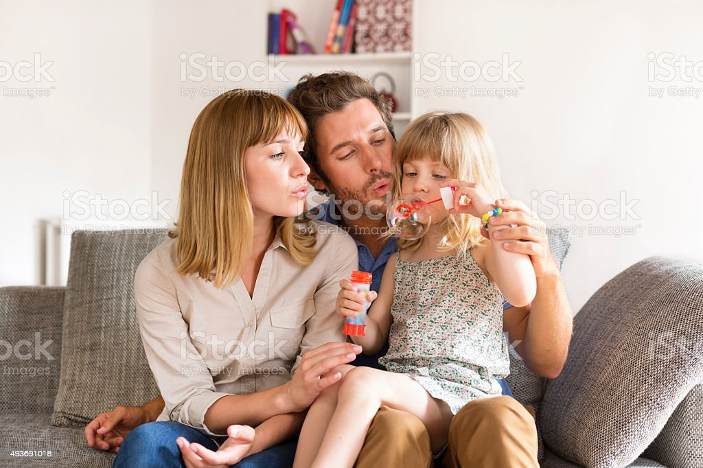 Cheerful parents and daughter blowing bubbles at home stock photo