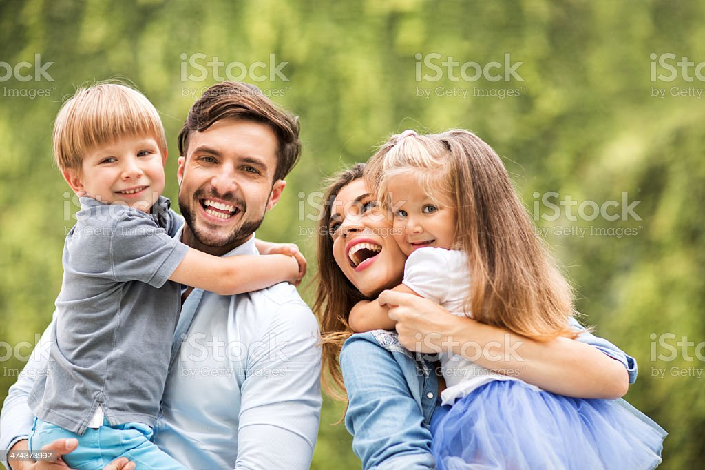 Cheerful parents having fun with their children outdoors. stock photo