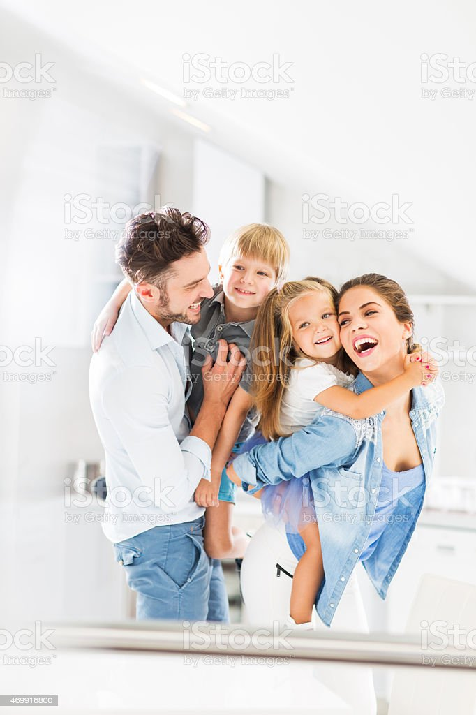 Cheerful parents having fun with their little children. stock photo