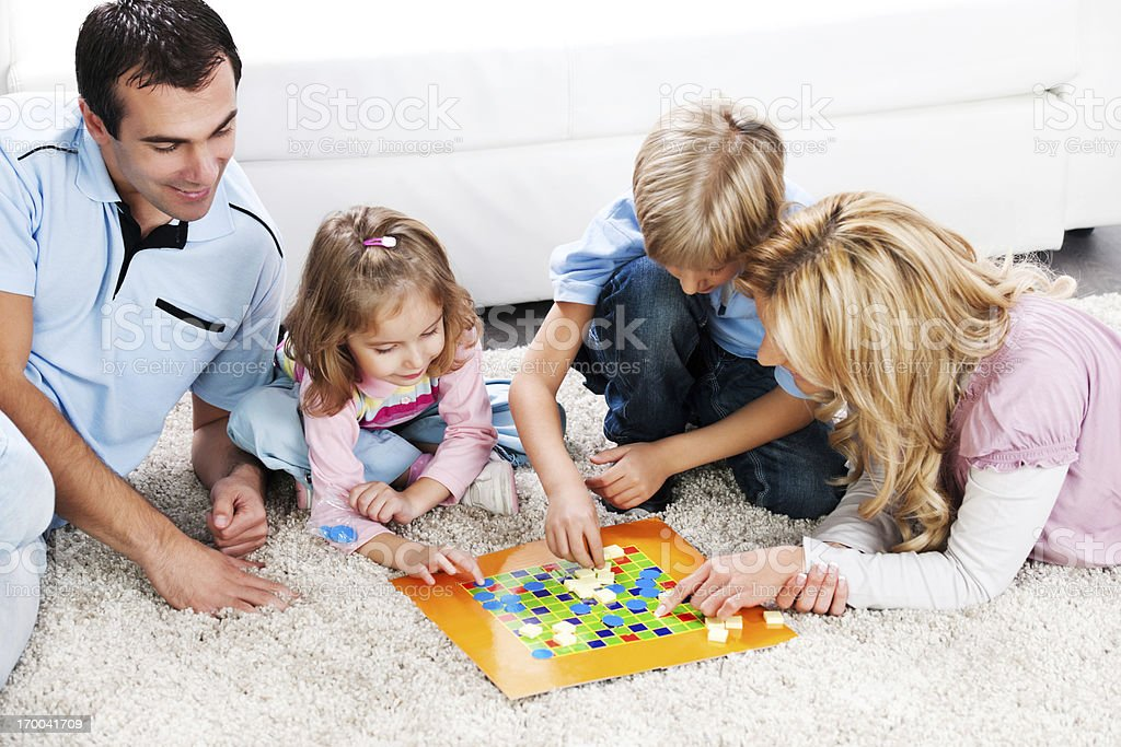 Cheerful parents playing board game with their children. stock photo