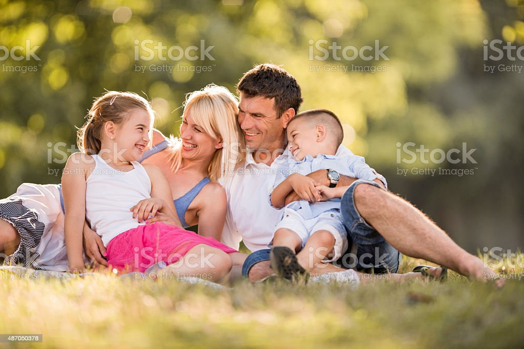 Cheerful parents talking to their children in the park. stock photo