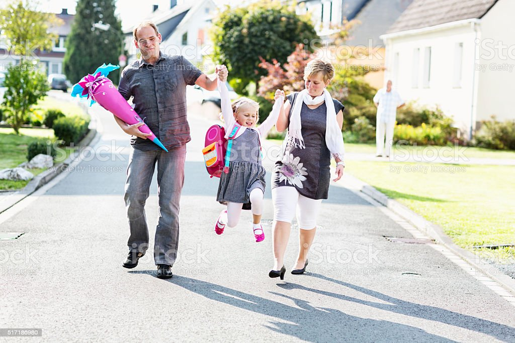 cheerful parents with schoolgirl swinging first day of school stock photo