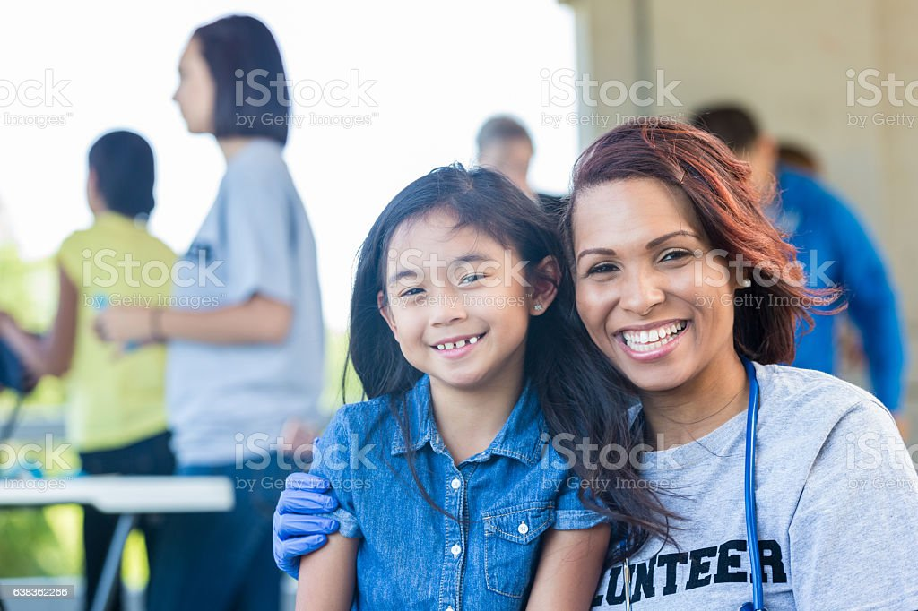 Cheerful pediatrician with young patient at outdoor health fair stock photo