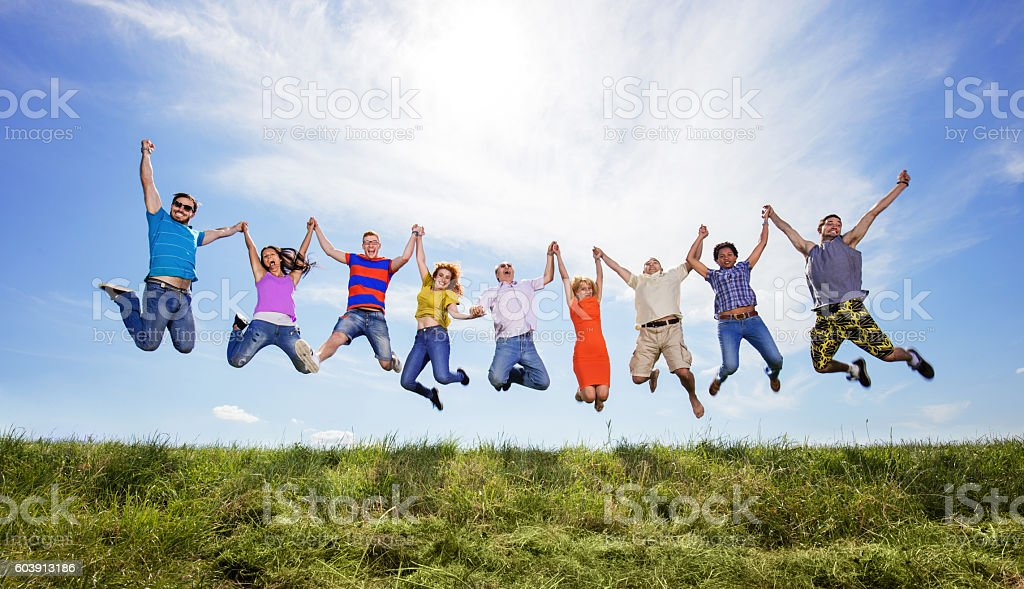 Cheerful people holding hands and jumping high up against sky. stock photo
