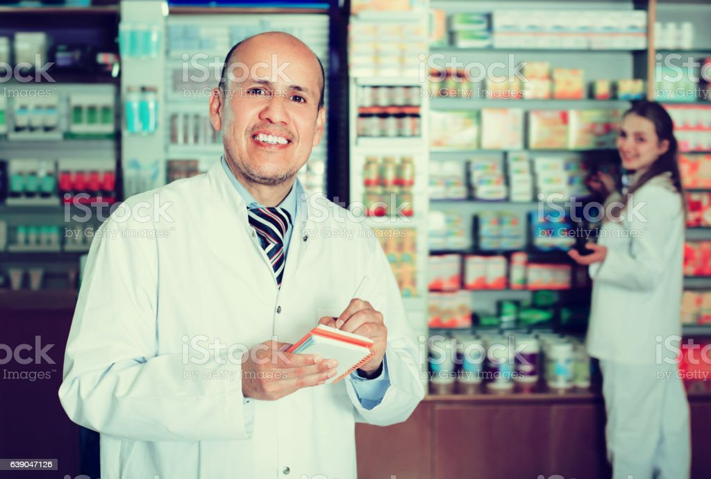 Cheerful pharmacist and female assistant helping stock photo