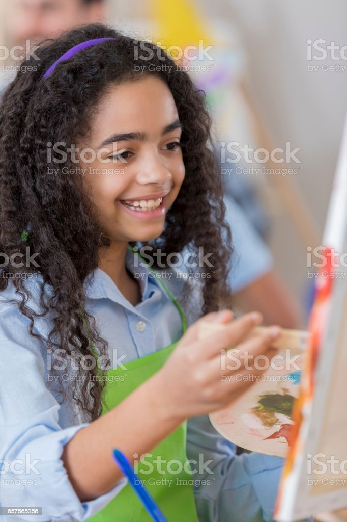 Cheerful preteen girl in art class stock photo