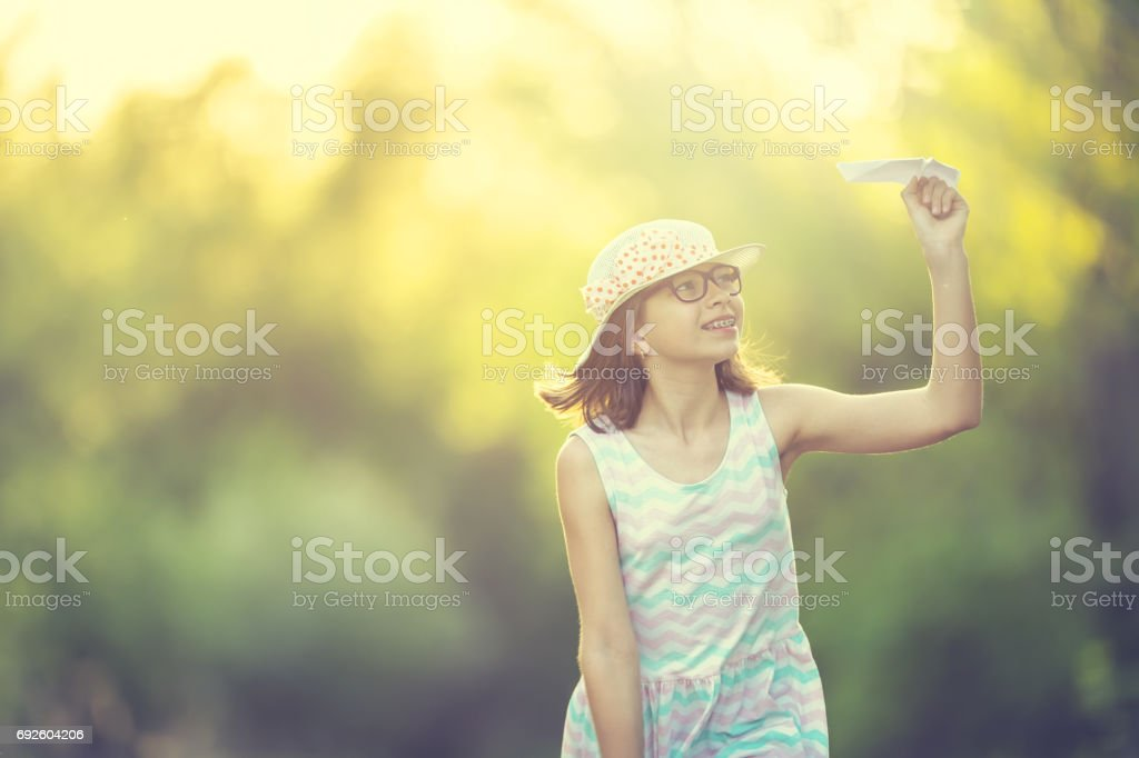 Cheerful pre-teen girl playing with paper plane on the park at sunrise. Girl with glasses and teeth braces stock photo