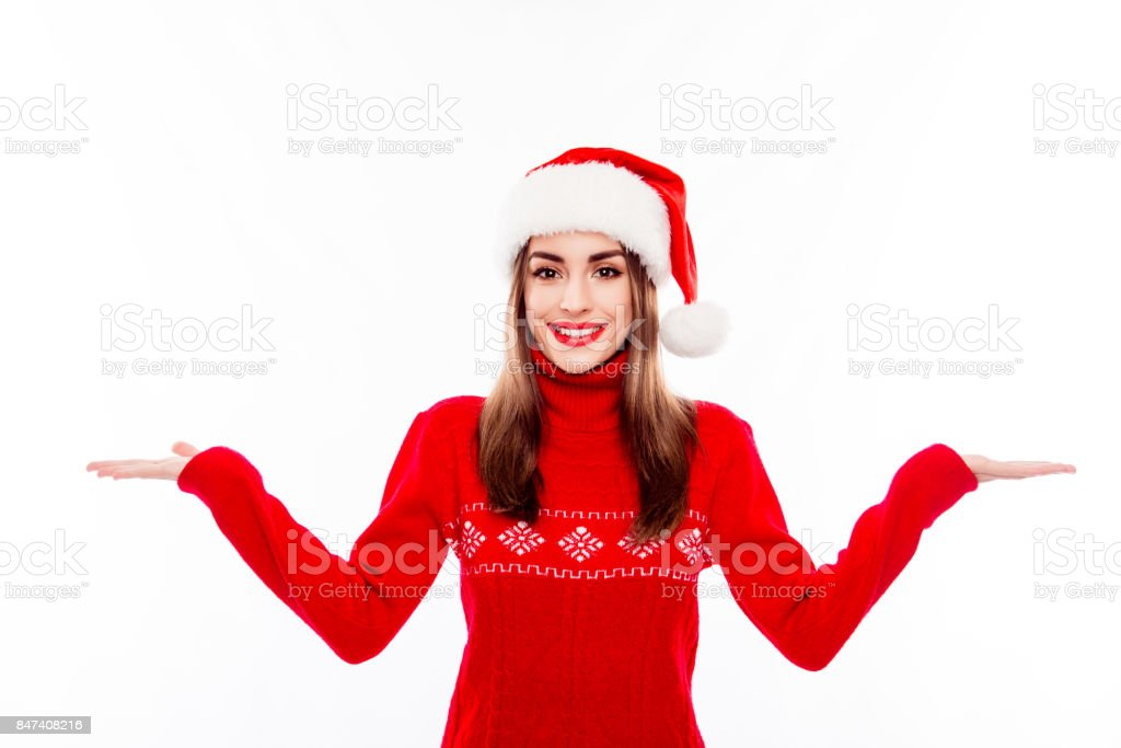 Cheerful pretty woman in santa hat making presentation of two products stock photo