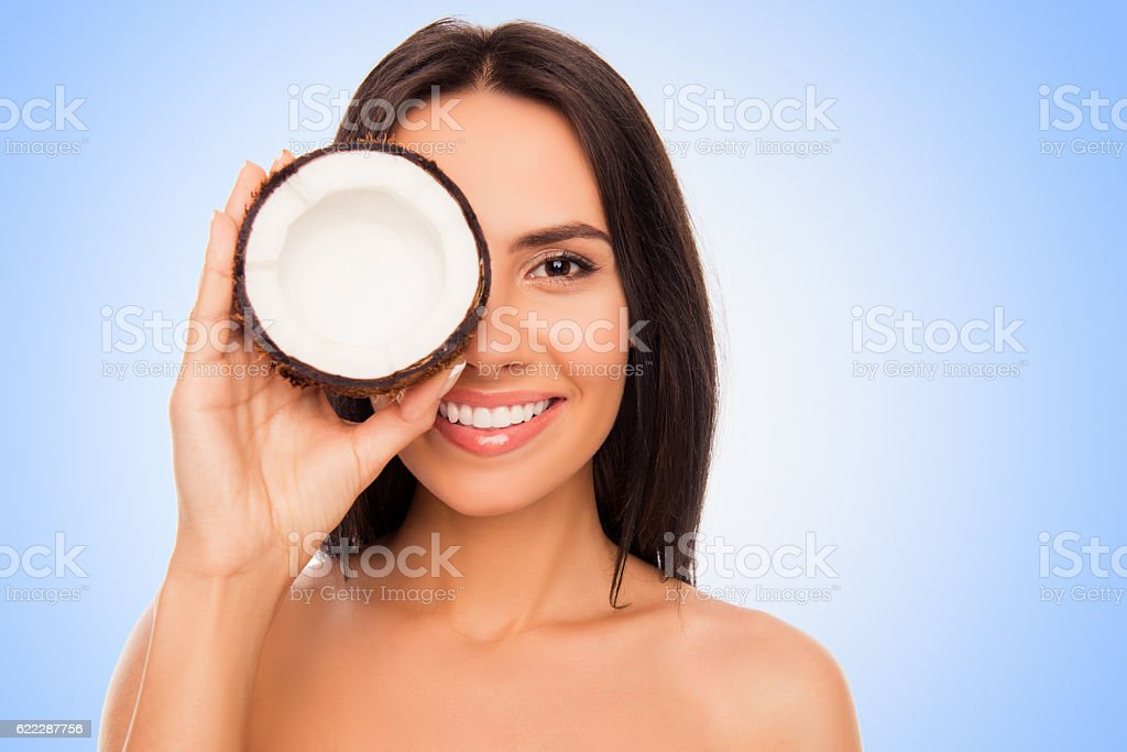 Cheerful pretty young woman holdind coconut near her eyes stock photo