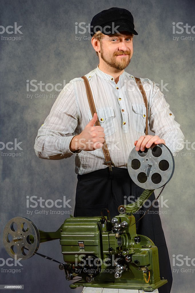 cheerful projectionist with film projector stock photo