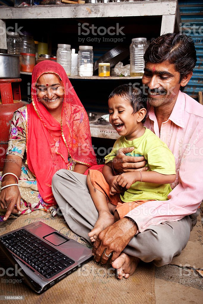 Cheerful Rajasthani Rural Indian Mother Father and Son Using Laptop royalty-free stock photo