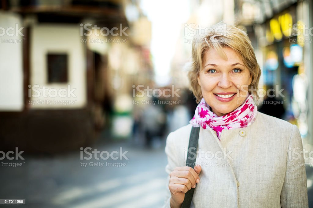 Cheerful retiree woman having a walk in city stock photo