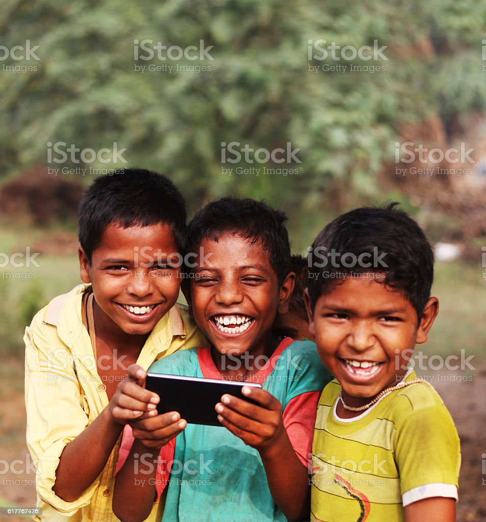 Cheerful rural children holding Smartphone stock photo