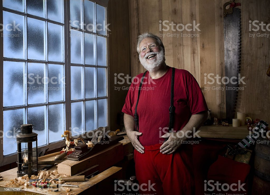 Cheerful Santa Claus Laughing in Christmas Workshop, Hands on Belly royalty-free stock photo