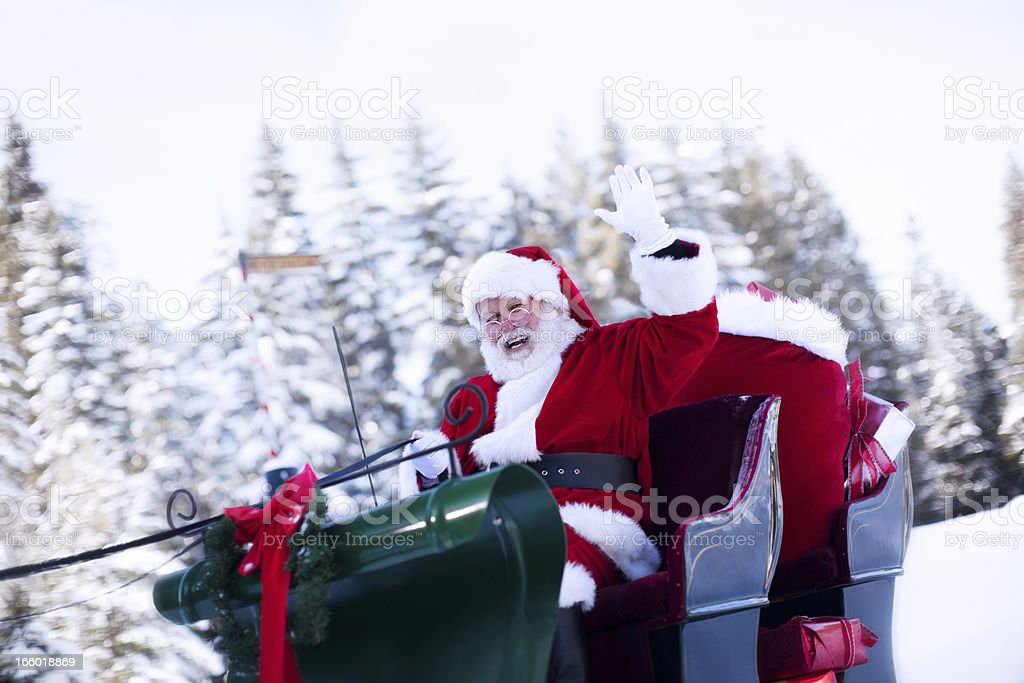 Cheerful Santa Claus Waving from Sleigh in Snow, Copy Space stock photo