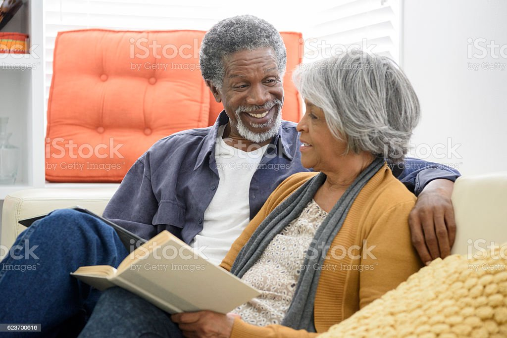 Cheerful senior African American couple laughing on sofa stock photo