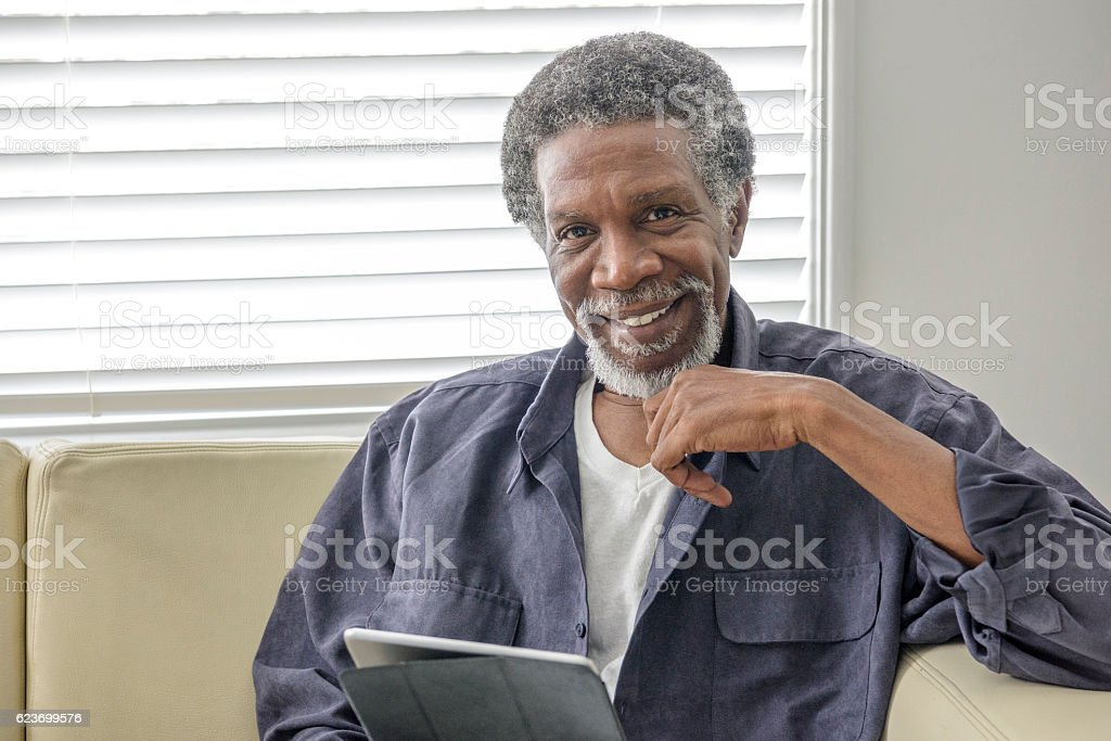 Cheerful senior African American man using tablet at home stock photo