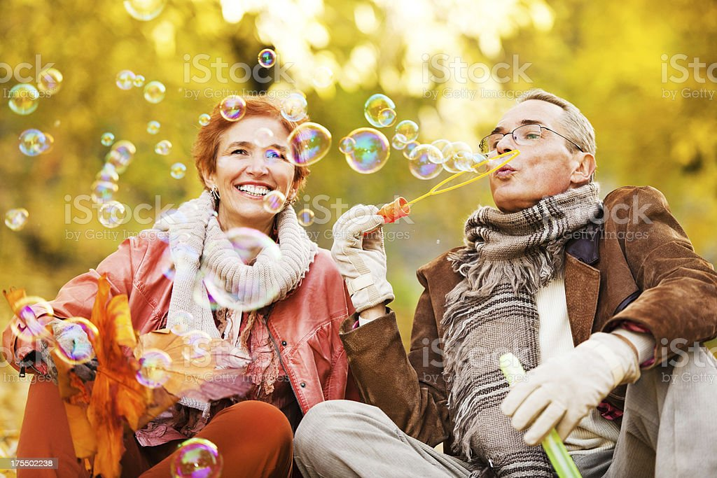 Cheerful senior couple blowing bubbles in park stock photo