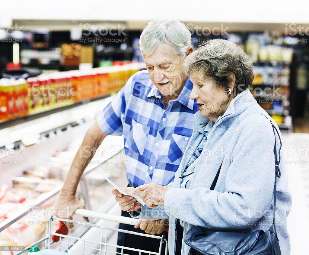 Cheerful senior couple check their shopping list in supermarket stock photo