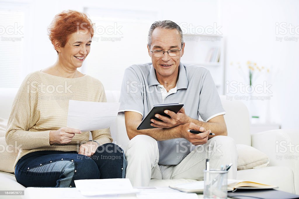 Cheerful senior couple counting a monthly bills at home. royalty-free stock photo