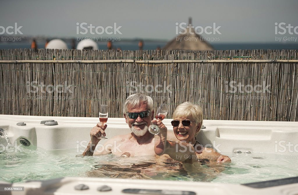 Cheerful Senior Couple Drinking Wine in Jacuzzi royalty-free stock photo