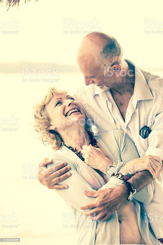 Cheerful Senior Couple Enjoying Summer Day on a Beach stock photo