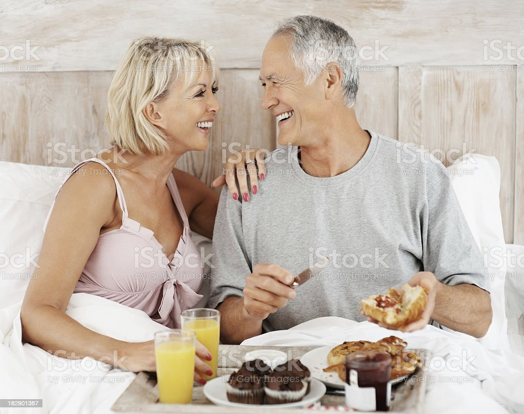 Cheerful senior couple having their breakfast in bed royalty-free stock photo