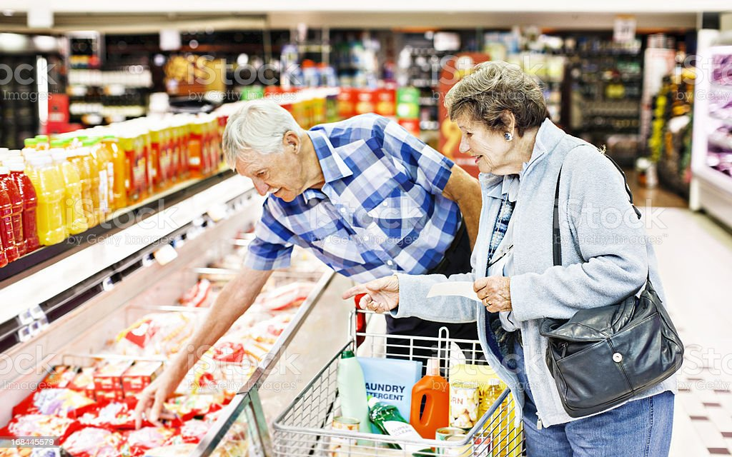 Cheerful senior couple make selection from supermarket fridge stock photo