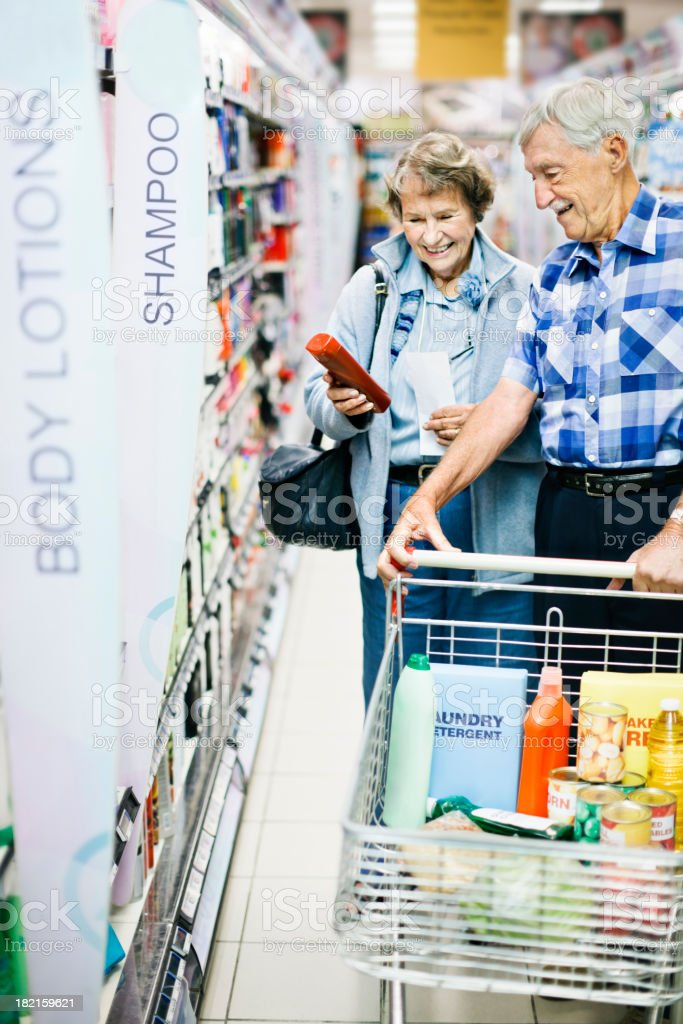 Cheerful senior couple shop for toiletries in supermarket stock photo