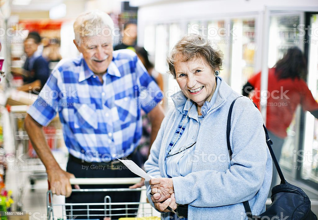Cheerful senior couple shopping in busy supermarket stock photo