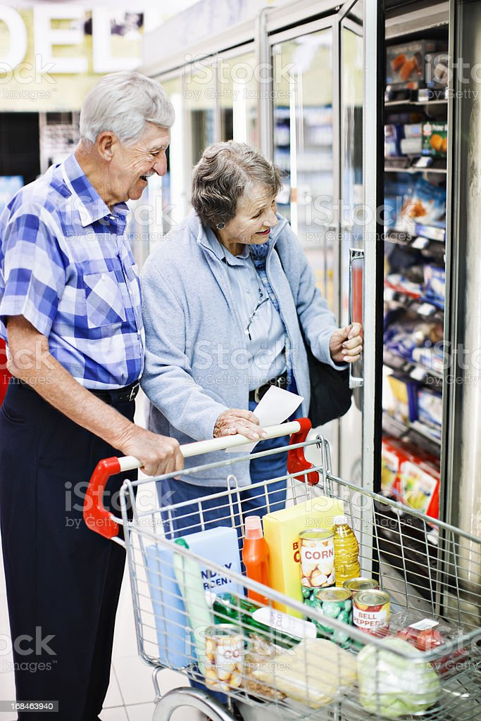 Cheerful senior couple shopping together check supermarket fridge stock photo