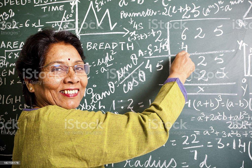 Cheerful Senior Indian Mathematics Teacher in a Classroom royalty-free stock photo