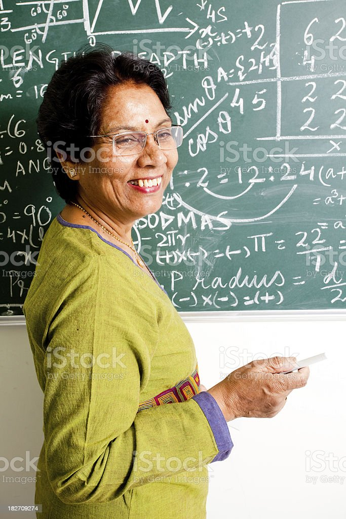 Cheerful Senior Indian Mathematics Teacher in a Classroom royalty-free stock photo