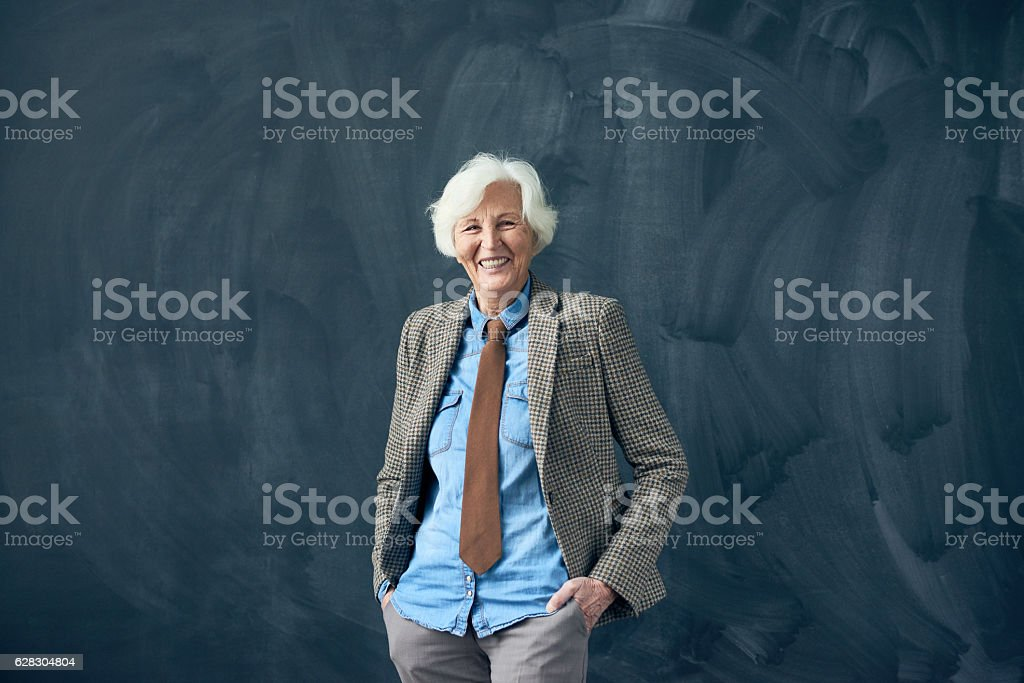Cheerful senior lecturer against blackboard stock photo