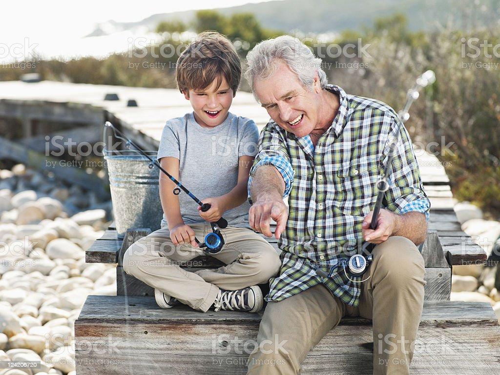 Cheerful senior man fishing with boy on pier stock photo