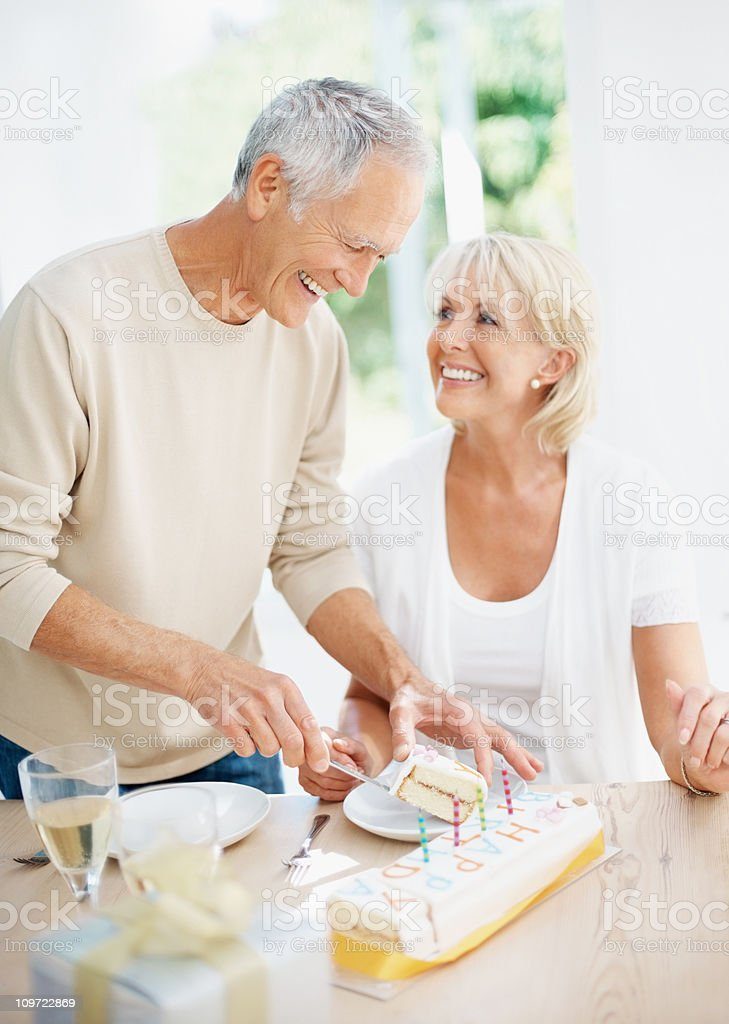 Cheerful senior man giving slice of cake to mature woman royalty-free stock photo