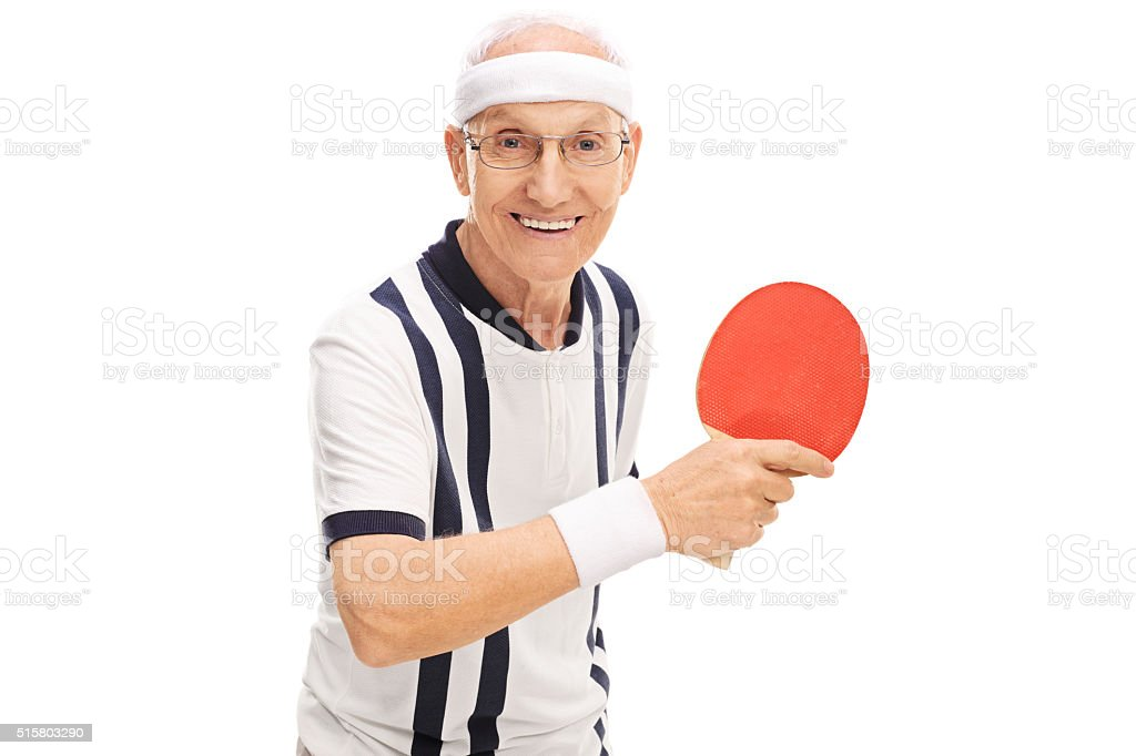 Cheerful senior man playing ping-pong stock photo
