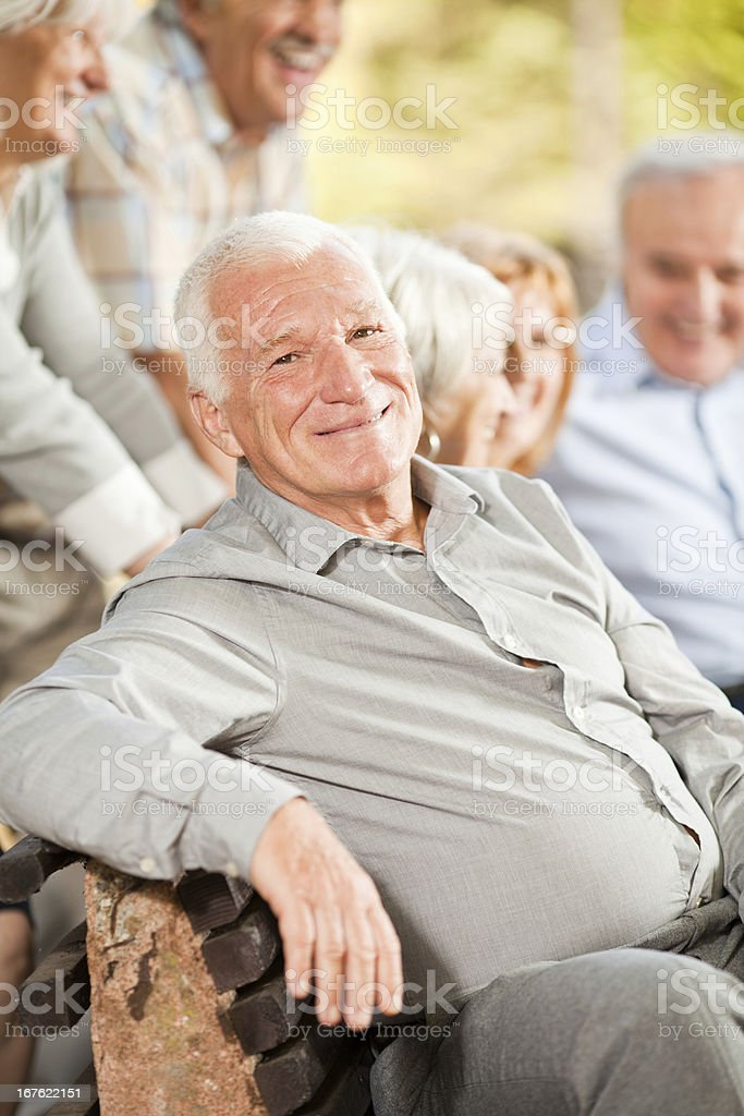 Cheerful senior man siting on bench in park royalty-free stock photo