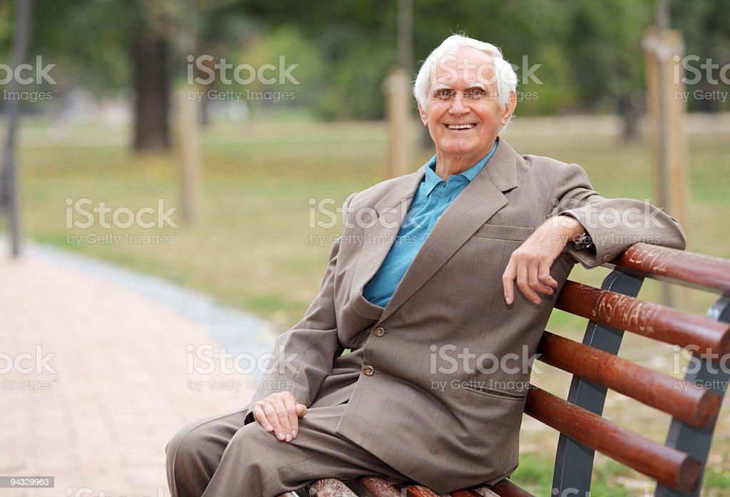 Cheerful senior man sitting outdoor on bench. royalty-free stock photo