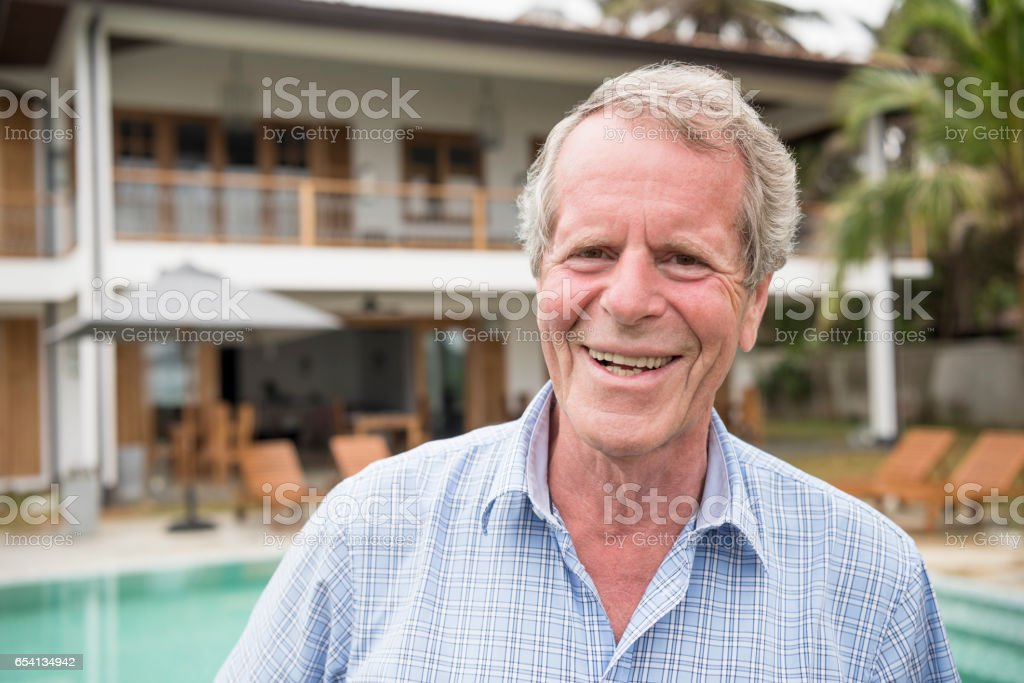 Cheerful senior man smiling towards camera, hotel in background stock photo