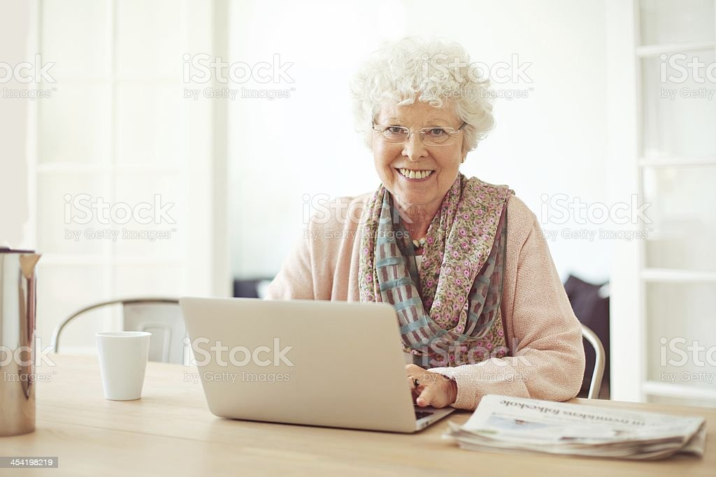 Cheerful Senior Woman at Home with Laptop stock photo