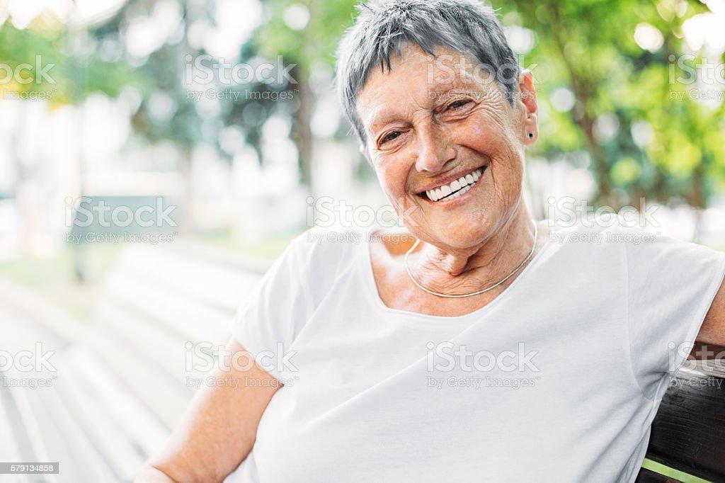 Cheerful senior woman at sunlight stock photo