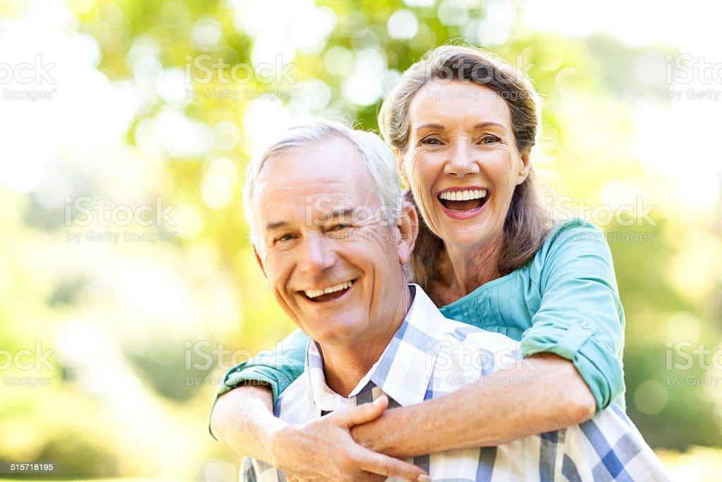 Cheerful Senior Woman Enjoying Piggyback Ride On Man stock photo